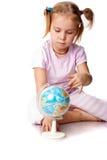 Menina bonita que joga com um globo imagem de stock