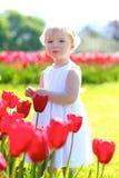Menina bonita que joga no jardim de flores Fotografia de Stock Royalty Free