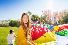 Menina bonita que joga o jogo do paraquedas com amigos Foto de Stock Royalty Free