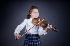 Menina bonita que joga o violino velho no fundo escuro fotos de stock