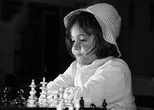 Menina bonita que joga a xadrez Fotos de Stock Royalty Free