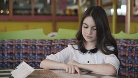 Menina bonita que lê o menu e que faz uma ordem 4K video estoque