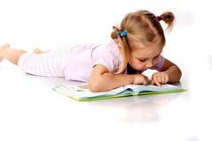 Menina bonita que lê um livro imagens de stock