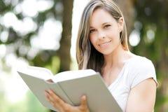 Menina bonita que lê um livro ao ar livre imagens de stock