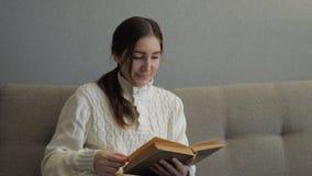 Menina bonita que lê um livro no sofá no interior acolhedor vídeos de arquivo