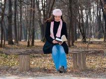 Menina bonita que lê um livro ao ar livre Fotos de Stock Royalty Free