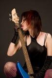 Menina bonita que lambe a guitarra Fotografia de Stock Royalty Free