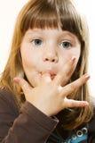 Menina bonita que lambe os dedos Fotos de Stock