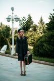Menina bonita que levanta na rua em um vestido do vintage com uma mala de viagem retro à disposição Sem retocar foto de stock