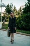 Menina bonita que levanta na rua em um vestido do vintage com uma mala de viagem retro à disposição Sem retocar imagem de stock