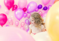 Menina bonita que levanta no estúdio onde lote dos balões Imagens de Stock