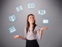 Menina bonita que manipula com ícones elecrtonic dos dispositivos Imagem de Stock Royalty Free