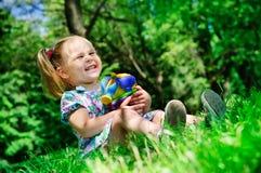 Menina bonita que mantem brinquedos novos para a caixa de areia ao ar livre Fotos de Stock
