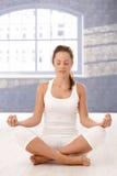 Menina bonita que meditating nos olhos do estúdio da ioga fechados imagens de stock