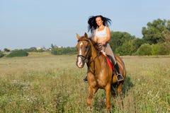 Menina bonita que monta um cavalo foto de stock royalty free