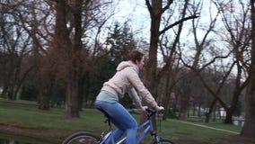Menina bonita que monta uma bicicleta video estoque