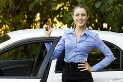 Menina bonita que mostra a chave do carro Imagens de Stock