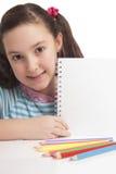 Menina bonita que mostra o espaço vazio no caderno Fotografia de Stock Royalty Free