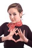 Menina bonita que mostra um coração com seus dedos Imagens de Stock