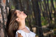 Menina bonita que olha acima com os olhos fechados nas madeiras Imagens de Stock