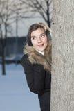 Menina bonita que olha além da árvore fotos de stock royalty free