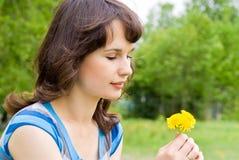 Menina bonita que olha as flores fotografia de stock royalty free