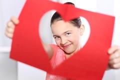 Menina bonita que olha através do cartão com um coração cortado fotos de stock