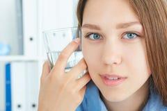 Menina bonita que olha a câmera que guarda um vidro da água Fotografia de Stock