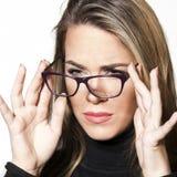 Menina bonita que olha com os glases da leitura, fazendo uma cara, tendo a dificuldade fotos de stock royalty free