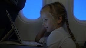 Menina bonita que olha desenhos animados na tabuleta vídeos de arquivo