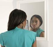 Menina bonita que olha em um espelho Fotos de Stock Royalty Free