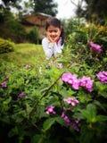Menina bonita que olha feliz sorrounded pela flor fotos de stock