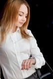 Menina bonita que olha o relógio Fotos de Stock Royalty Free