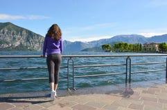 Menina bonita que olha a paisagem ensolarada do lago e das montanhas no fundo exterior Conceito saudável do estilo de vida do cur fotografia de stock royalty free