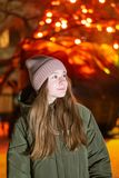 Menina bonita que olha para baixo na rua da cidade da noite contra o contexto da montra de incandescência Fundo com bokeh Copie o imagem de stock