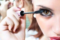 Menina bonita que põe a composição sobre seus olhos foto de stock