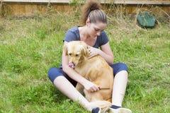 Menina bonita que penteia a pele do cão exterior Fotos de Stock