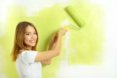 Menina bonita que pinta uma parede Fotos de Stock Royalty Free