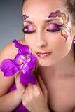 Menina bonita que prende a íris roxa Foto de Stock Royalty Free