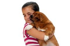 Menina bonita que prende um cão pekingese pequeno Imagem de Stock Royalty Free