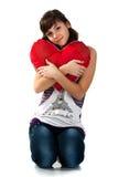 Menina bonita que prende um coração vermelho fotos de stock