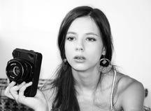 Menina bonita que prende uma câmera Fotografia de Stock Royalty Free