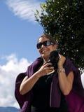 Menina bonita que prende uma câmera digital do dslr Foto de Stock