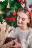 Menina bonita que prende uma caixa de presente Natal, época dos milagre fotografia de stock