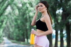 Menina bonita que prepara-se para movimentar-se no parque Com garrafa de garrafa térmica à disposição imagens de stock