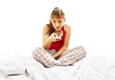Menina bonita que presta atenção à tevê na cama imagens de stock