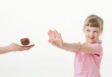 Menina bonita que regecting um bolo de chocolate Imagem de Stock