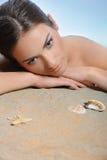 Menina bonita que relaxa na areia com escudos foto de stock