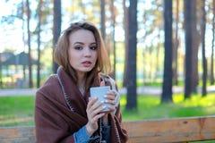 Menina bonita que relaxa no café do parque e da bebida fotografia de stock royalty free