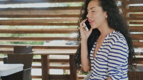 A menina bonita que ri e aprecia a conversação no telefone filme